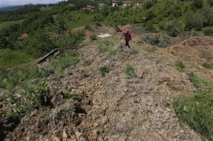 A Bosnian man walks on a broken road after a landslide which swept away eight houses near Kalesija, Bosnia, 150 kms north of Sarajevo, Sunday May 18, 2014.