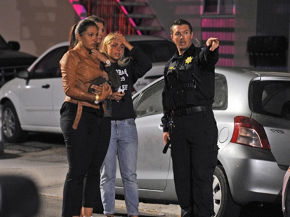 People speak to a police officer after a mass shooting near the campus of the University of Santa Barbara in Isla Vista, Calif., Friday, May 23, 2014.