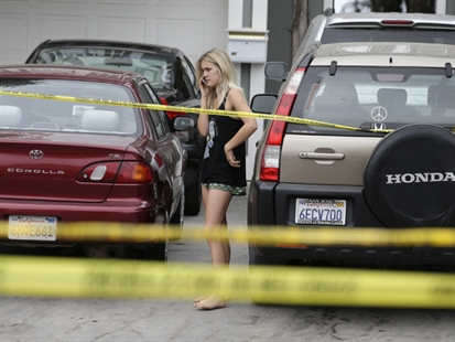 A college student talks on the phone near the scene of a shooting on Saturday, May 24, 2014, in Isla Vista, Calif.