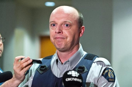 RCMP officer Damien Theriault holds back tears while addressing the media during a press conference at City Hall in Moncton, N.B. on Wednesday June 4, 2014.