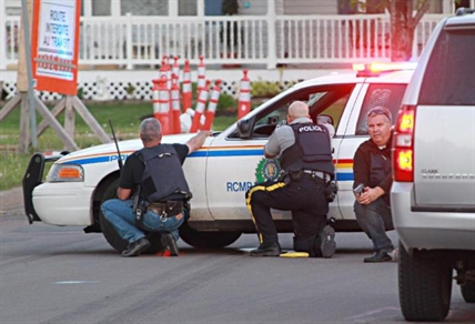 Police officers take cover behind their vehicles in Moncton, New Brunswick, on Wednesday June 4, 2014. Three police officers were shot dead and two others injured Wednesday in the east coast Canadian province of New Brunswick, officials said, and authorities were searching for a suspect.