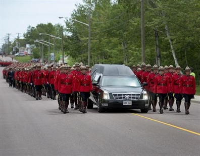 The funeral procession for the three RCMP officers who were killed in the line of duty, makes its way to the regimental funeral at the Moncton Coliseum on Tuesday, June 10, 2014.