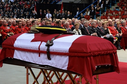 Dignitaries, including (front row, from left) Gov. General David Johnston, his wife Sharon, Prime Minister Stephen Harper, N.B. Lt. Gov. Graydon Nicholas, N.B Premier David Alward and wife Rhonda, RCMP commissioner Bob Paulson, attend the RCMP regimental funeral on Tuesday, June 10, 2014 in Moncton, N.B.