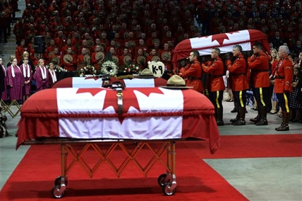 Pallbearers carry the casket of RCMP officer Const. Fabrice Georges Gevaudan, 45, from Boulogne-Billancourt, France, into a regimental funeral for three slain officers in Moncton, N.B., Tuesday, June 10, 2014.