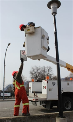 City of Penticton workers remove signs from street lights alongside the Okanagan Lake waterfront today. These lights will be replaced entirely with LED versions.