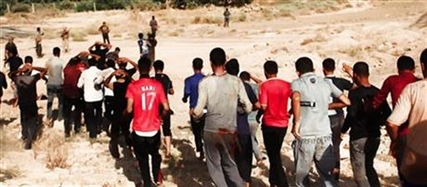 This image posted on a militant website on Saturday, June 14, 2014 appears to show militants from the al-Qaida-inspired Islamic State of Iraq and the Levant (ISIL) leading captured Iraqi soldiers wearing plain clothes to an open field moments before shooting them in Tikrit, Iraq.