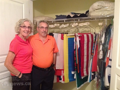 Bifano and his wife, Mavis, stand in front of the closet where all the flags are stored - neatly organized and labeled according to geographic location.