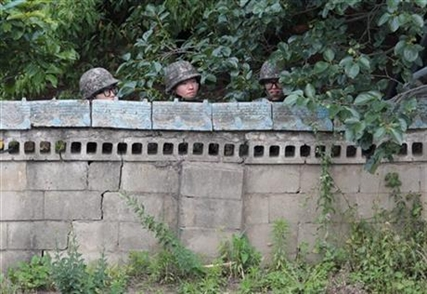 South Korean army soldiers hide behind a wall of a private house during a gunfight with a South Korean conscript soldier.