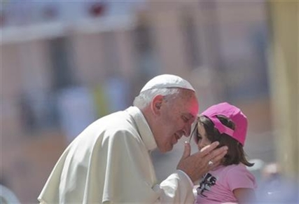Pope Francis kisses a girl in front the Duomo of Cassano allo Jonio, southern Italy, Saturday, June 21, 2014.