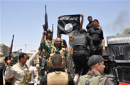 Iraqi security forces hold up a flag of the Islamic State in Iraq northeast of Baghdad, Iraq on Saturday, June 28, 2014.