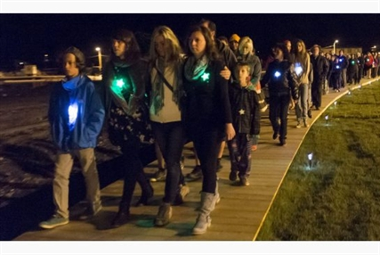 Family and friends walk along the crash site, observing a moment of silence at 1:15 a.m. on Sunday, July 6, 2014 when a runaway train derailed in the centre of Lac-Megantic killing 47 people.