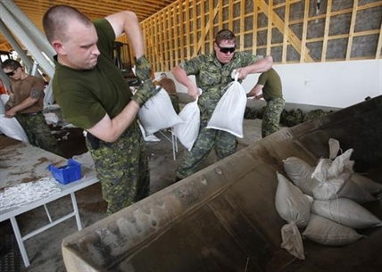 Military from Shilo work to fill and load sandbags in Portage La Prairie, Man., Saturday, July 5, 2014.