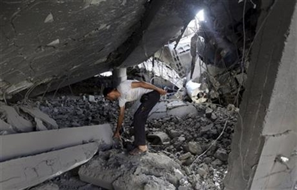 A Palestinian searches the ruins of the Al-Tawfeeq mosque after it was hit by an Israeli missile strike Saturday, July 12, 2014.