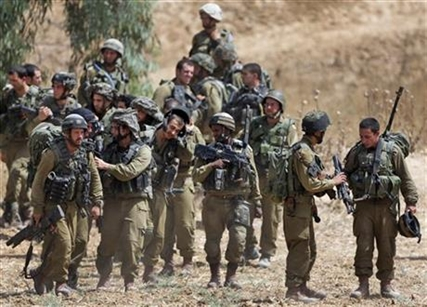 Israeli infantry soldiers get ready to walk to their armored personnel carriers to take up new positions on the Israel-Gaza border, Saturday, July 12, 2014.
