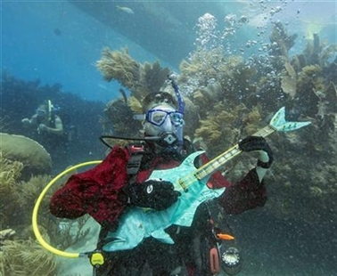 Mike Limerick pretends to play a mock musical instrument at the Lower Keys Underwater Music Festival on Saturday, July 12, 2014.