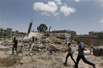 Palestinians walk past one of the houses of the al-Batsh family, demolished by an Israeli strike earlier last week, on Sunday, July 13, 2014.