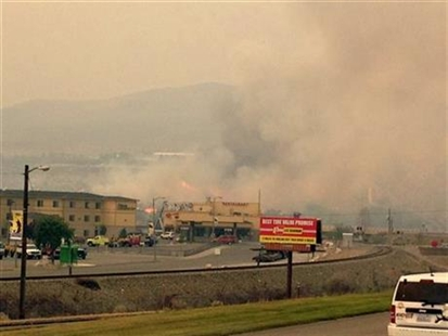 Flames and smoke fill the air along the hillside above the river, in Pateros, Wa, Friday, July 18, 2014.