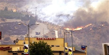 Flames creep down a hillside in view of businesses Friday, July 18, 2014, in Pateros, Wash.