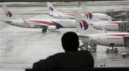 A visitor looks out from the viewing gallery as Malaysia Airlines aircrafts sit on the tarmac at the Kuala Lumpur International Airport.