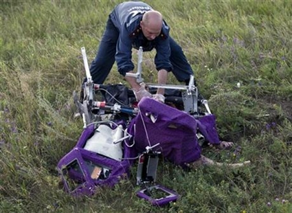An emergency worker cuts through aircraft seat belts to free the body of a victim at the crash site of Malaysia Airlines Flight 17 in eastern Ukraine, Saturday, July 19, 2014.
