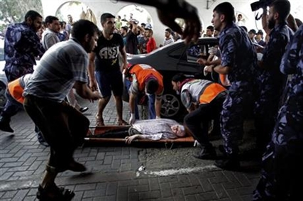 Palestinian medics carry a wounded woman to an emergency room at Shifa hospital in Gaza City, Sunday, July 20, 2014.