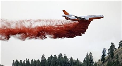 A DC-10 air tanker drops fire retardant over a wildfire Saturday, July 19, 2014, near Carlton, Wash.
