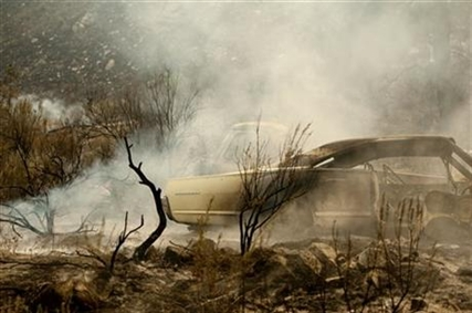 A collection of vintage cars smolder after a wildfire burnt through them on Friday, July 18, 2014, near Malott, Wash.