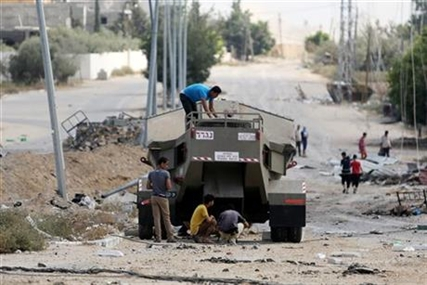 Palestinian men climb on Israel's military vehicle that was left behind by the forces in Gaza City's Shijaiyah neighborhood, Saturday, July 26, 2014.