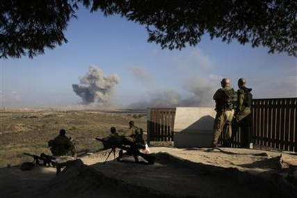 Israeli soldiers observe bombings of Gaza before a 12-hour cease-fire, seen from the border of Israel and the Gaza Strip, Saturday, July 26, 2014.