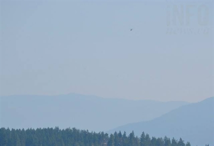 A B.C. Wildfire helicopter flies above Armstrong, B.C.