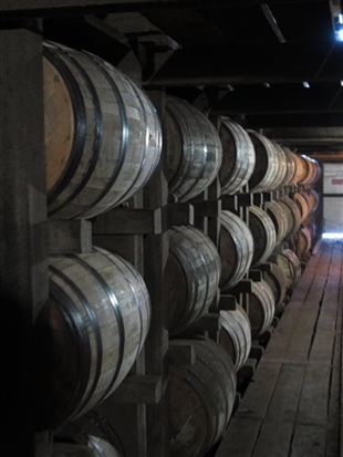 In a July 24, 2014 photo, bourbon supplies age in barrels at the Jim Beam distillery in Clermont, Ky.