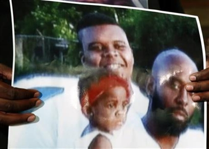 This undated family photo provided by the Brown Family and held by Michael Brown Sr., shows Michael Brown Sr., at right, his son, Michael Brown, top left, and a young child. Michael Brown, 18, was shot and killed in a confrontation with police in the St. Louis suburb of Ferguson, Mo, on Saturday, Aug. 9, 2014.
