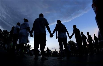 People stand in prayer on Wednesday, Aug. 20, 2014, in Ferguson, Mo.