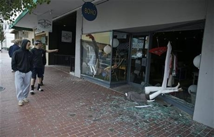 People walk past a tumbled mannequin and broken storefront window on First Street following an earthquake Sunday, Aug. 24, 2014, in Napa, Calif.
