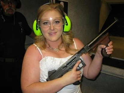 This July 28, 2012 file photo provided by Bob MacDuff shows Lindsae MacDuff holding an automatic weapon at the Gun store in Las Vegas after her