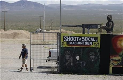 A man closes off an entrance to the Last Stop outdoor shooting range Wednesday, Aug. 27, 2014, in White Hills, Ariz.
