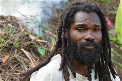 "In this Sept. 2, 2014 photo, Joseph Williams, a former Jamaican soldier who is now the ""scribe"" for the School of Vision Rastafarian group, is shown taking a break from clearing steep farmland at the their isolated retreat in the Blue Mountains that tower over Kingston, Jamaica."