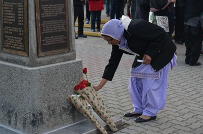 A family member lays a rose on the memorial on April 6, 2013 in commemoration of nine loved ones murdered in 1996.