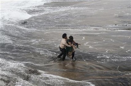 A man, left rescues a woman who fell in water due to strong tidal waves prior to a cyclone on the Bay of Bengal in India, Sunday, Oct. 12, 2014.