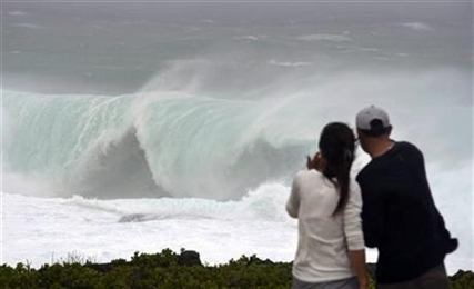 A couple watches a huge wave at a cape in Yomitan Village, Japan's southern island of Okinawa Sunday, Oct. 12, 2014.