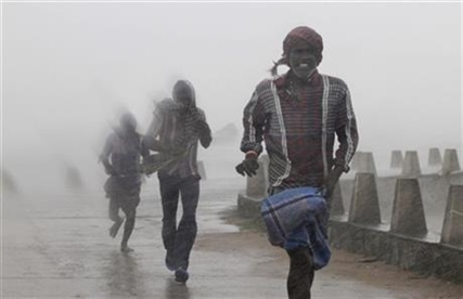 People run for shelter as heavy rain and wind gusts rip through the Bay of Bengal in India, Sunday, Oct. 12, 2014.