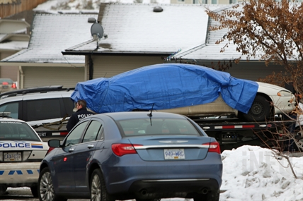 The car involved in the shooting of Cpl. Jean-Rene Michaud is removed from the garage of a house on Raven Drive.