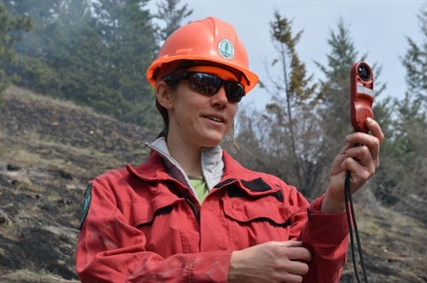 Katherine Ladyman of the Okanagan Shuswap Natural Resource District uses an instrument to check wind speed, relative humidity and temperature before the burn begins.
