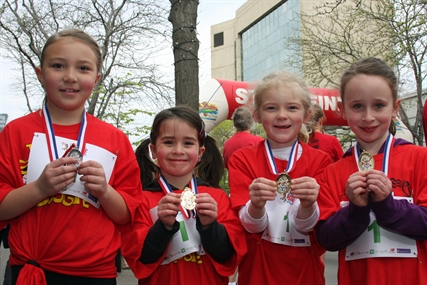Presley, Sophie, Lizzie and Madison show off their medals after finishing the Mini Boogie portion of Boogie the Bridge Sunday morning.