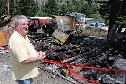Robbie Kilborn of Olalla stands next to a destroyed Mercedes Benz. His brother's motor home and other vehicles were destroyed in a fire Sunday night.