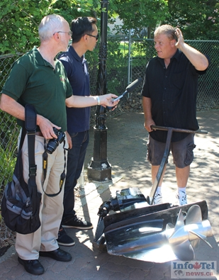 Boat owner Rene (right), a Penticton resident, is questioned by the media on Wednesday afternoon. He was making the boat lighter for retrieval by removing engine and other components. Rene said what happened was an accident and he's glad no one was hurt or killed.