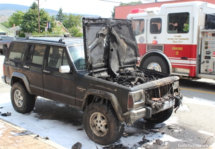A Penticton Fire and Rescue truck speeds away after dousing a burning Jeep Cherokee Laredo on Padmore Avenue East Wednesday afternoon. RCMP remained on scene.