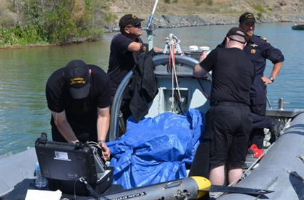 Divers from the Pacific Fleet Diving Unit preparing to head out for another sweep of Kalamalka lake.