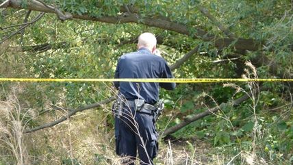 A member of the RCMP Identification Unit takes photos of the scene where a body was found this afternoon.