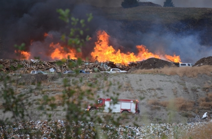 Flames rise after a wood grinder malfunctioned at the Vernon landfill and sparked a large fire which has spread to nearby grass.